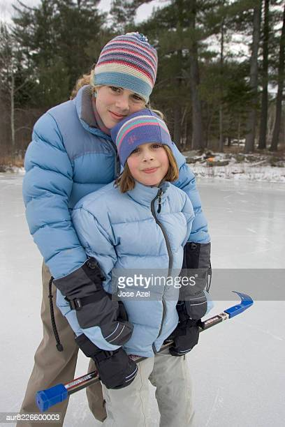 Two Girls looking at camera while standing on frozen pond, New England, USA