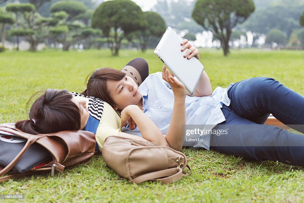 Two girls looking at tablet on grassland : Stock Photo