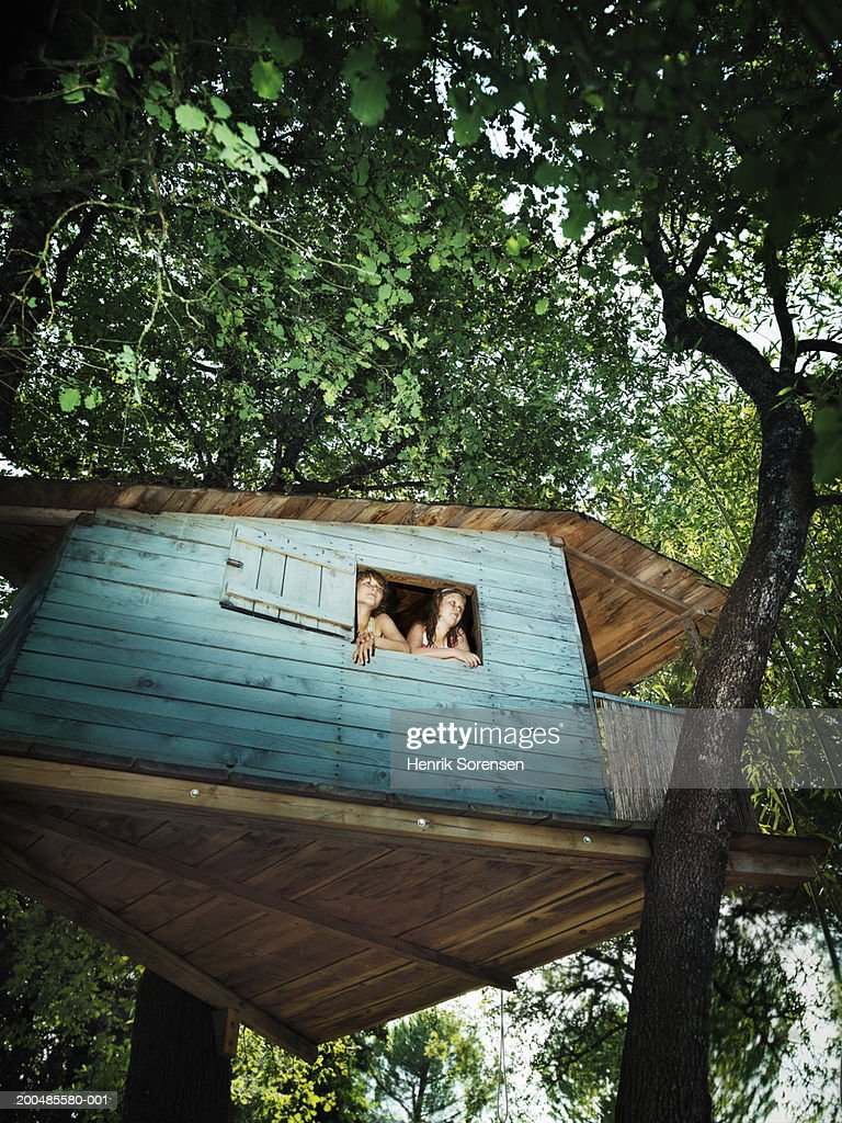 Two girls (7-12) looking out of window in blue tree house, low angle : Stock Photo