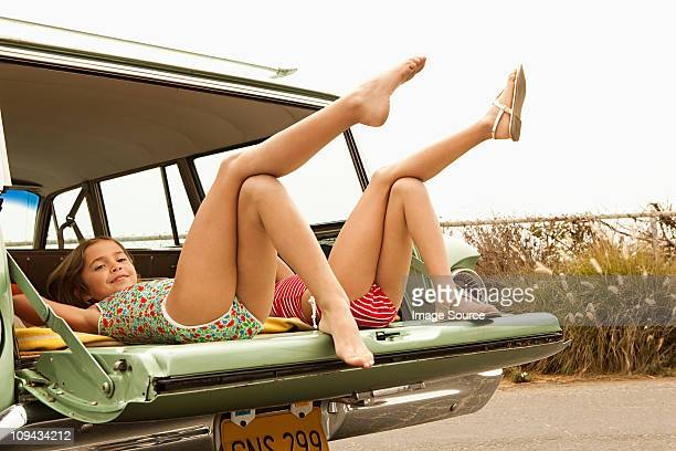 Two girls lying in estate car with legs in the air