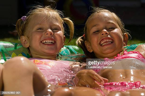 Two girls (4-6) lying in paddling pool, laughing