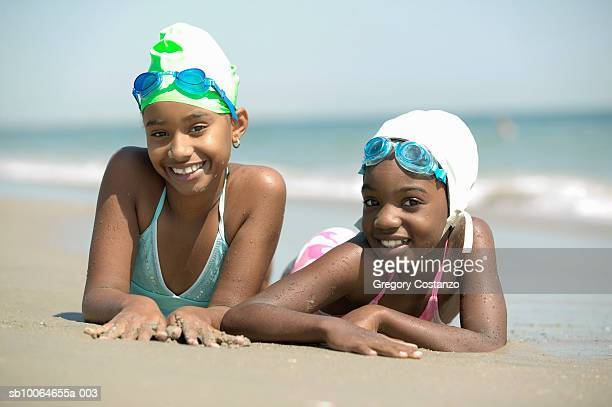Two girls (8-9) lying on beach, smiling, portrait, (focus on foreground)