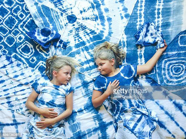 Two girls lying on variety of tie dyed articles