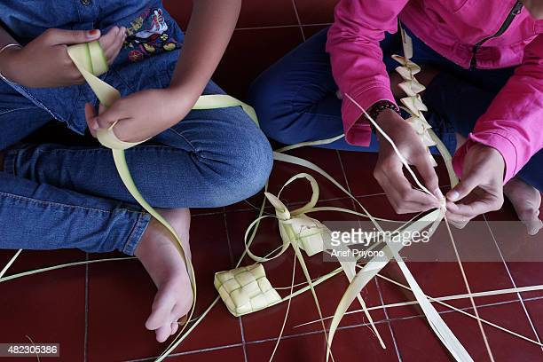 Two girls make the woven palm leaf wrappings for 'Ketupat' in the village of Durenan Celebrating the 'Ketupat Feast' has been an annual tradition in...