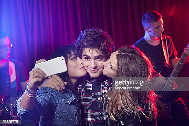 Two girls making a selfie with a boy