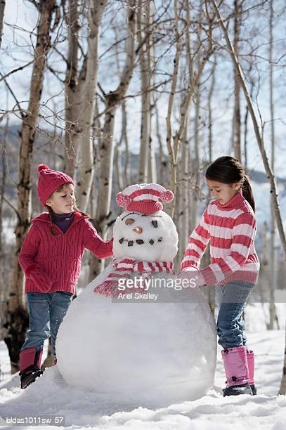 Two girls making a snowman
