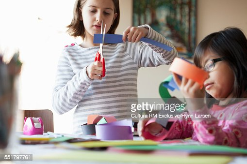 Two girls making paper chains