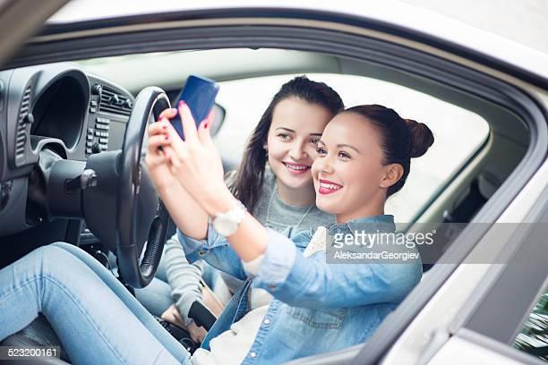 Deux jeunes filles faire des autophotos et de s'amuser dans la voiture