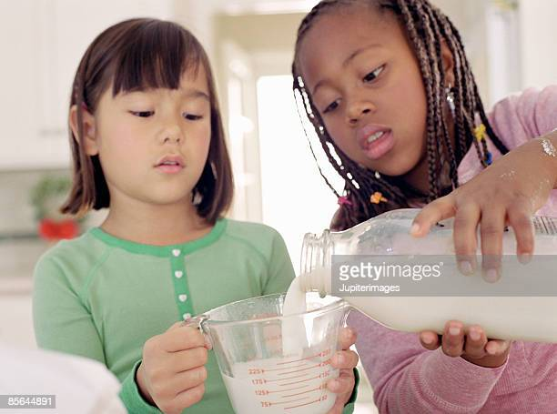Two girls measuring milk