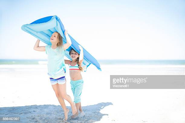Two girls on beach carrying a lilo