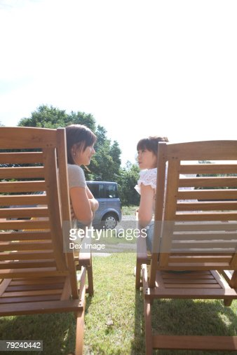 Two girls on deck chairs, chatting : Stock Photo