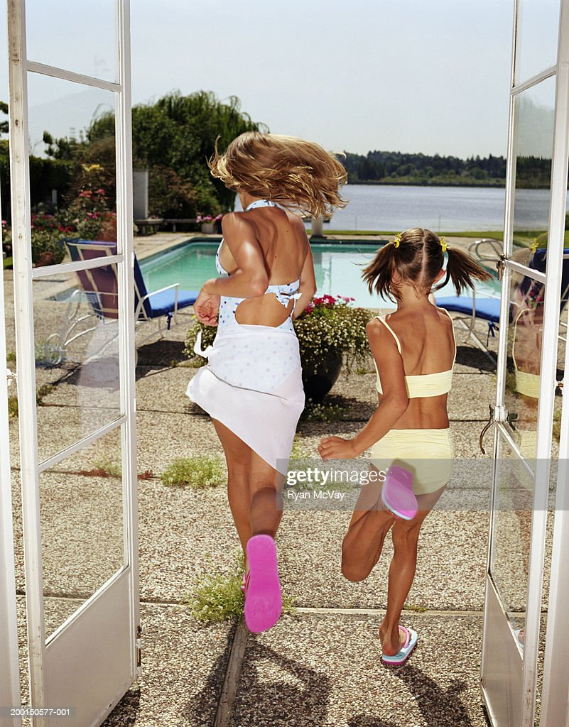 Two girls (9-12) on patio, running toward swimming pool, rear view : Stock Photo