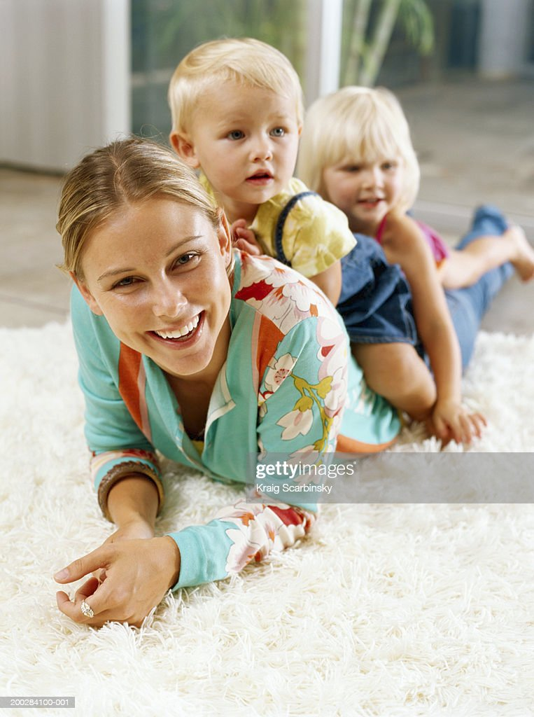 Two girls (21-24 months) on woman's back, lying on rug, smiling : Stock Photo