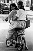 'Two girls onboard a Ciao Piaggio motorscooter turn around and look at the camera with curiosity Italy 1979 '