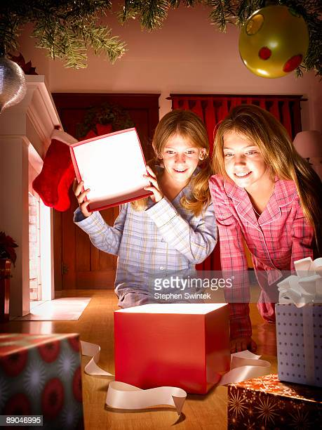 Two girls opening a glowing christmas present