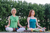two girls or women practicing yoga in nature