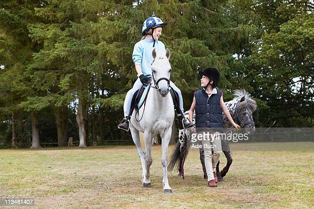 Two girls out riding ponies