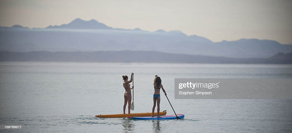 two girls paddle boarding, morning calm : Stock Photo