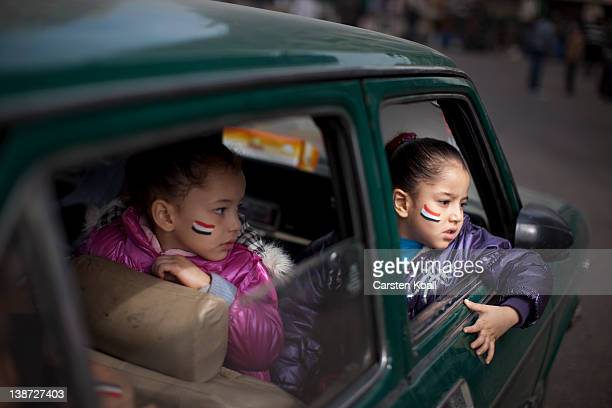 Two girls painted with the egyptian national colors sit in a car in Tharir Square on February 10 2012 in Cairo Egypt Egyptian people await the...