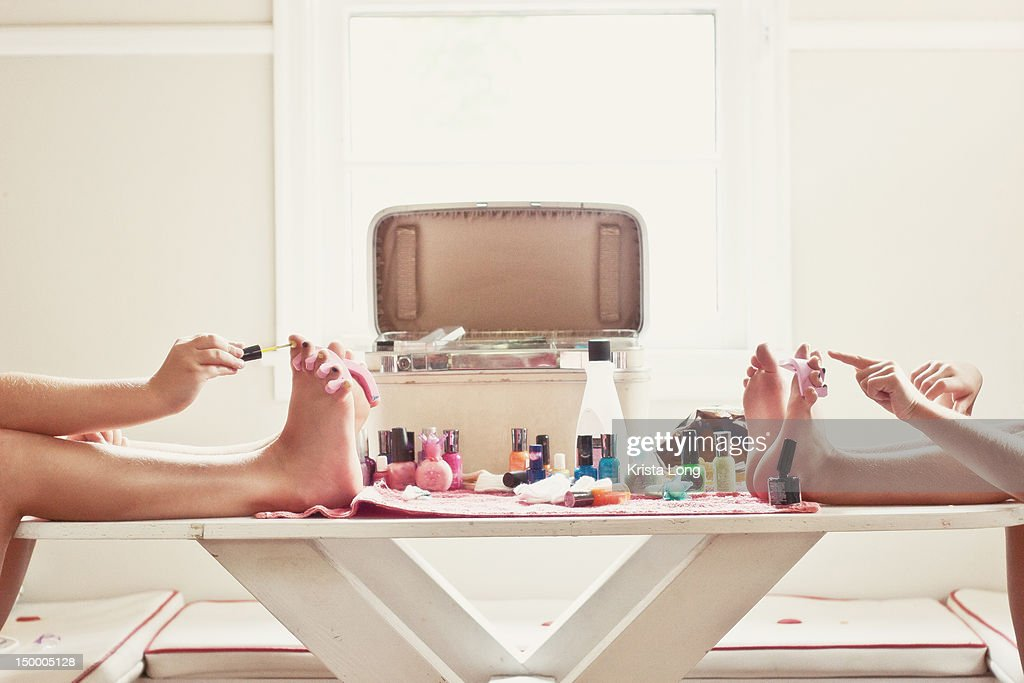 Two girls painting their toenails. : Stock Photo