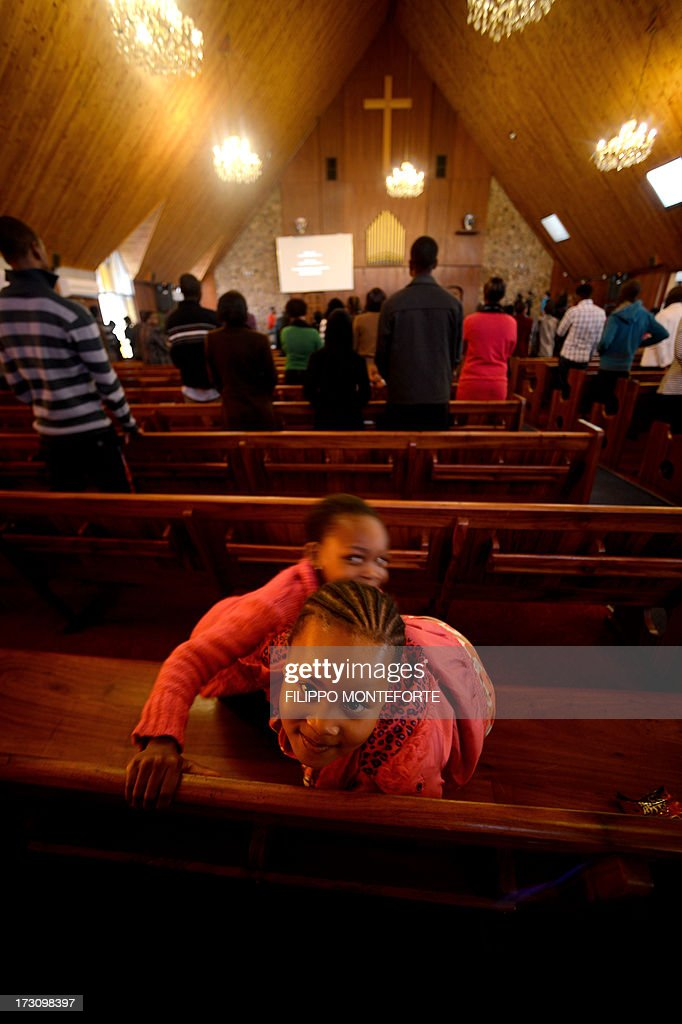Two girls play as people pray in Pretoria's Petra church during a gospel mass on July 7, 2013. Former South African president Nelson Mandela lays in critical condition in Pretoria's the Medi Clinic Heart hospital where emotional crowds gathered outside, as relatives and clan elders made preparations for the revered former South African leader's final journey. Singing supporters amassed outside the Pretoria hospital where the 94-year-old anti-apartheid hero was fighting for his life. AFP PHOTO / Filippo MONTEFORTE