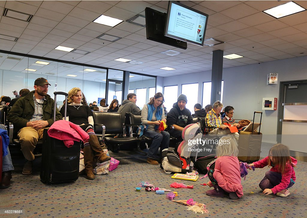 Two girls play with dolls on the floor as their parents wait to board their planes at the Salt Lake City international Airport on November 27, 2013 in Salt Lake City, Utah. A wintry storm system that is covering much of the nation is threatening to wreak havoc on holiday travel .