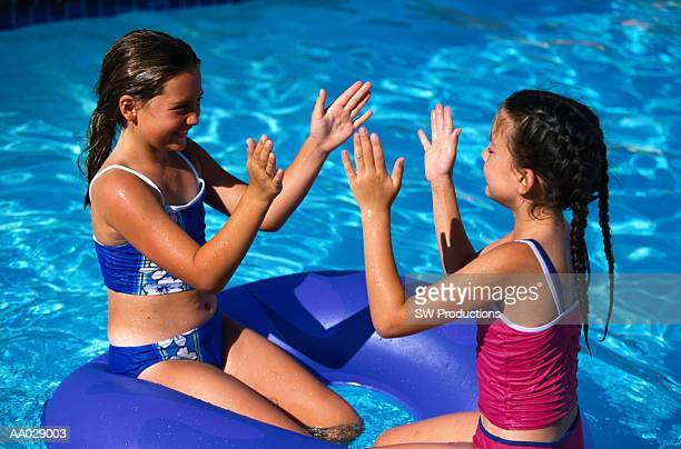 Two Girls Playing a Clapping Game on an Inflatable