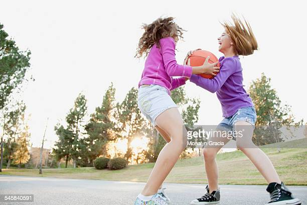 Two girls (10-12) playing basketball on court