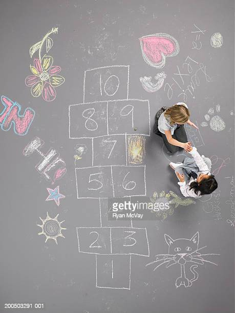 Two girls (8-10) playing clapping game beside hopscotch squares