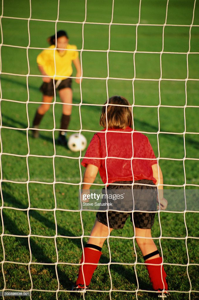 Two girls (9-11) playing football, one in goal, view through net : Stock Photo