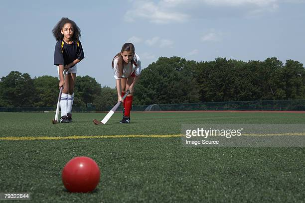 Two girls playing hockey