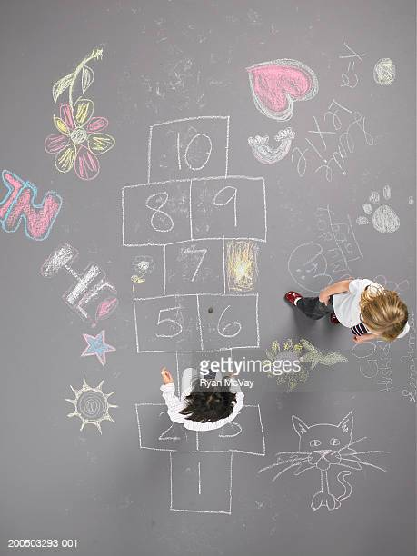 Two girls (8-10) playing hopscotch, overhead view