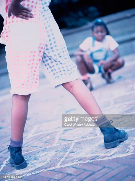 Two Girls Playing Hopscotch