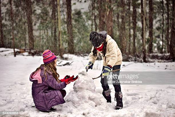 Two girls playing in a snow and hail storm.