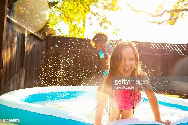 Two girls playing in garden paddling pool