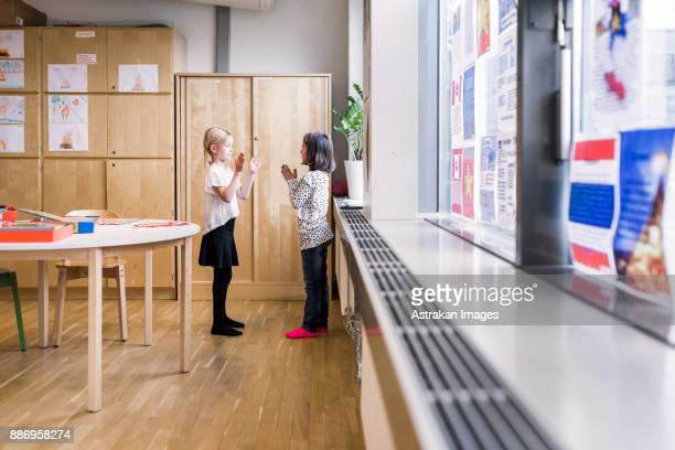 Two girls (8-9) playing in school