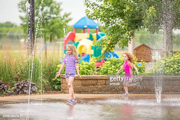 Two Girls Playing In Water Fountains At Park