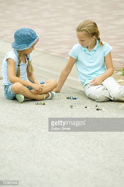 Two girls playing marbles in street