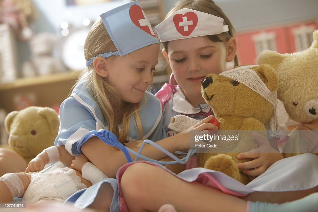 two girls playing nurse with toys : Stock Photo