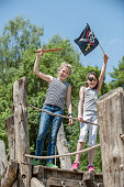 Two girls playing on pirate ship in adventure playground, Bavaria, Germany