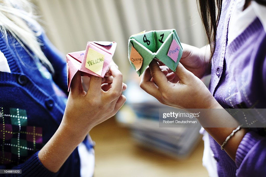 Two girls playing origami fortune game : Stock Photo