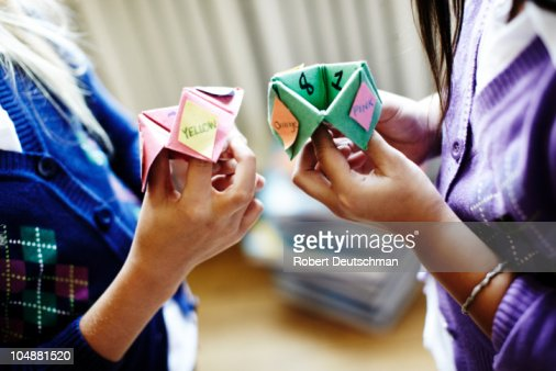 Two girls playing origami fortune game : Stockfoto