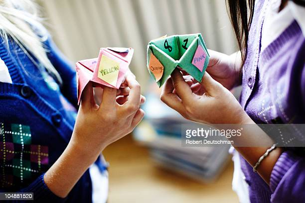Two girls playing origami fortune game
