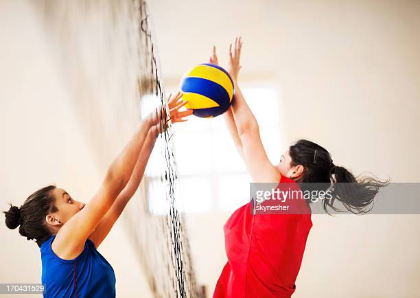 Two girls playing volleyball.
