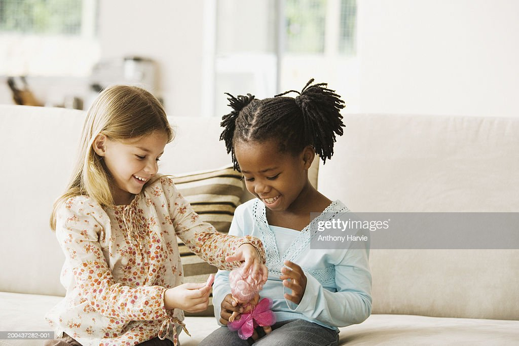 Two girls (4-6) playing with doll in living room, smiling