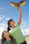 Two girls (5-9) playing with kite at wind farm