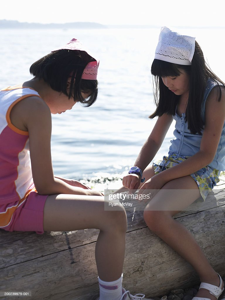 Two girls (8-10) playing with shells on log at beach, side view : Stock Photo