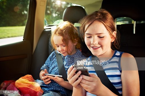 Two girls playing with smart phone in car : Foto de stock