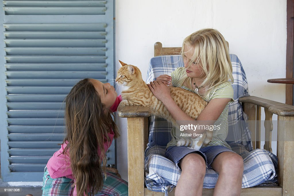 Two girls playing with their cat. : Stock Photo