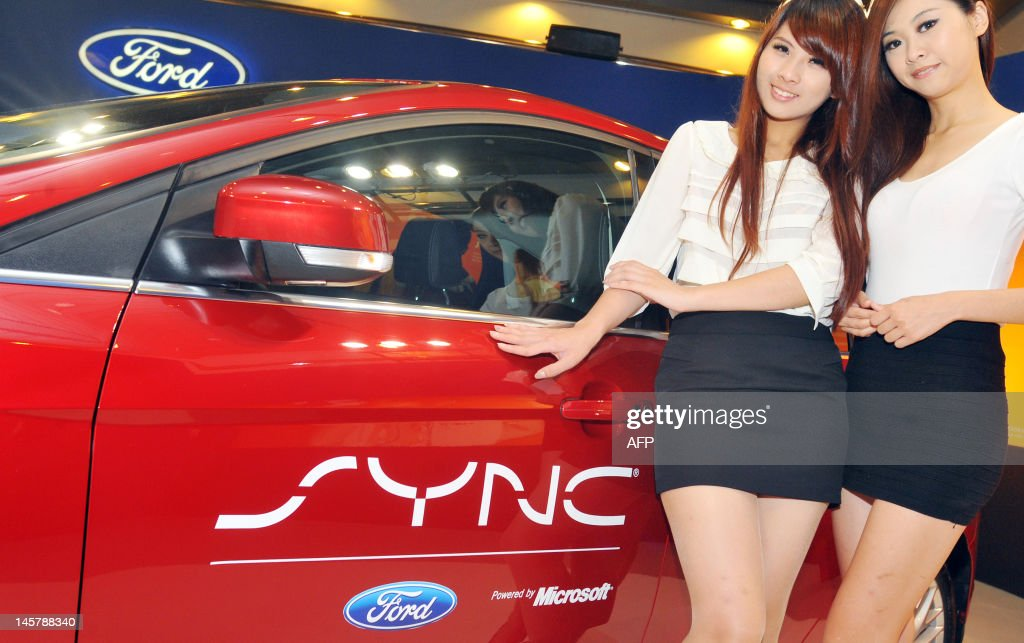 Two girls pose nest to the a Ford Focus car, equipped with will Microsoft powered SYNC, an in-car connectivity system, at the 2012 Computex in Taipei on June 6, 2012. Computex is Asia's leading IT trade fair. AFP PHOTO / Mandy CHENG